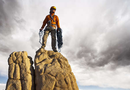 conquer: Climber on the summit after a challenging ascent.