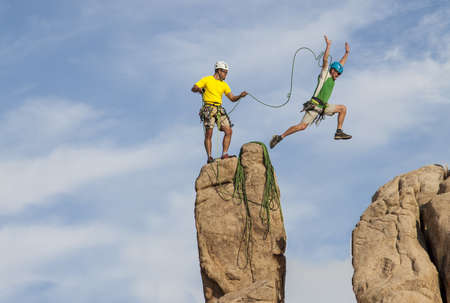 conquer: Team of male climbers conquer the summit of a challenging rock spire.
