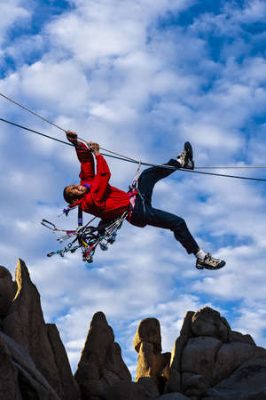Male, ethnic rock climber pulls himself across a tyrollean traverse  photo
