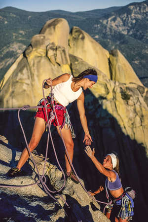 conquer: Team of female climbers conquer the summit of a challenging rock spire