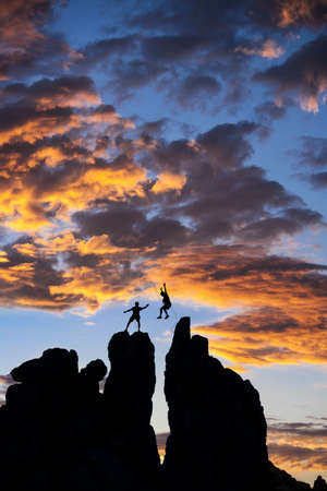 conquer: Team of climbers conquer the summit of a challenging rock spire