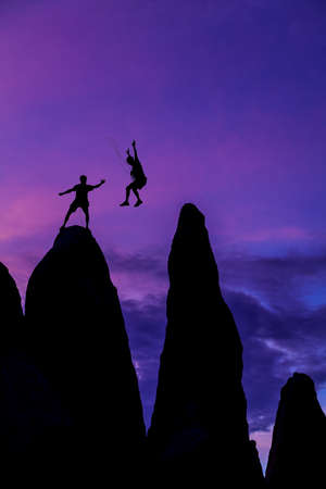Team of climbers conquer the summit of a challenging rock spire. photo