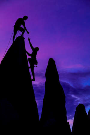 conquer: Team of climbers conquer the summit of a challenging rock spire. Stock Photo