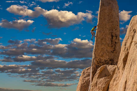 tenacity: Rock climber clings to the edge of a challenging cliff in Joshua Tree National Park.