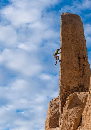 Rock climber clings to the edge of a challenging cliff in Joshua Tree National Park. photo