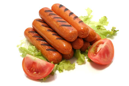 grilled sausages on green lettuce with two tomatoes quarter Stock Photo