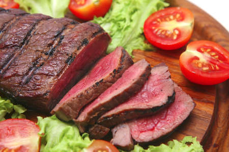 grilled red beef meat on wooden plate photo