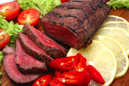 roast sliced meat served with vegetables photo