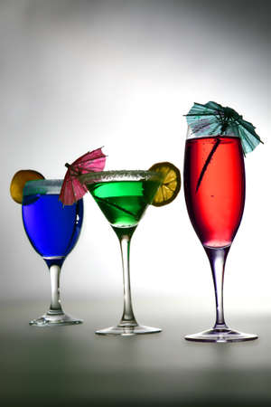 three colored coctails in row on lighted background photo