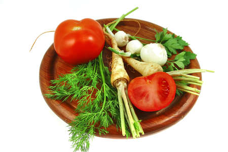 green vegetables with tomato on wooden plate photo