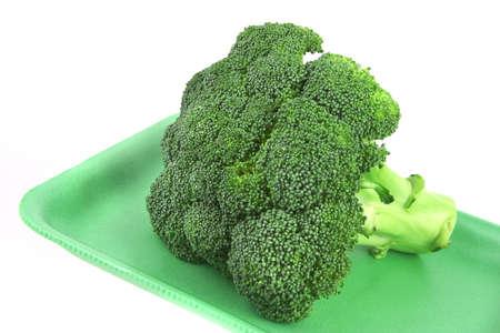 broccolli: one green fresh raw broccoli on plastic plate