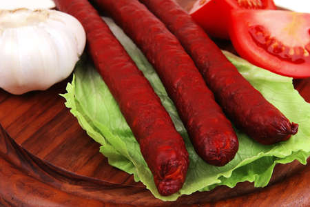 pork sausages on cut plate with vegetables photo