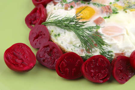fried eggs and small red eggplant on green dish photo