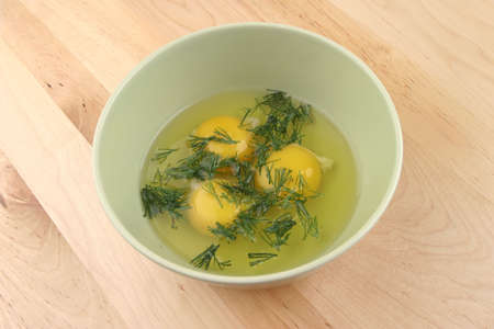 broken raw eggs and fennel inside bowl photo