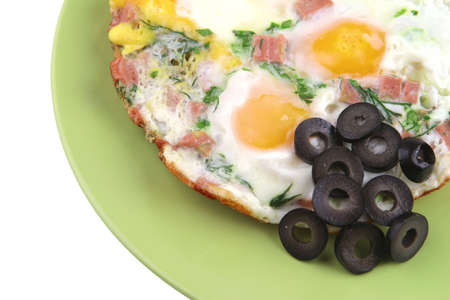 eggs fried with sausage and black olives on green dish photo
