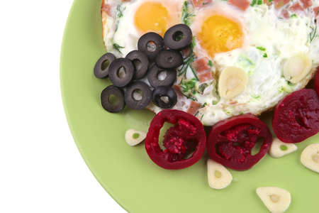 eggs fried with red eggplants and black olives on green dish photo