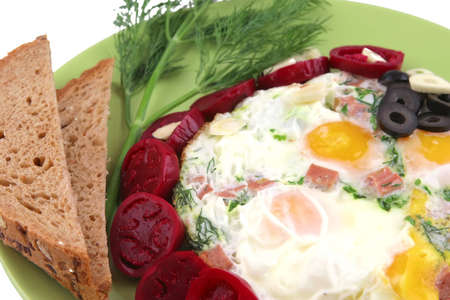 fried eggs served on green dish with olives photo