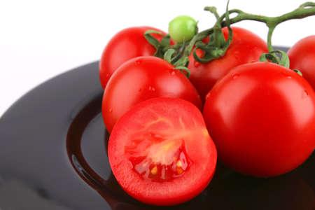 fresh uncooked tomato close up on black dish photo