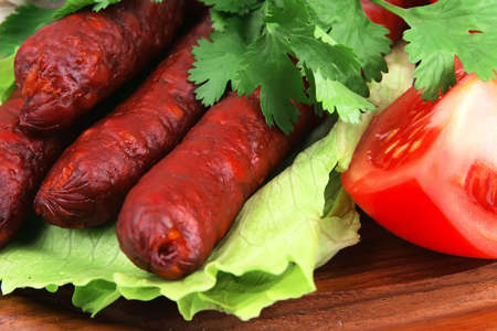 red beef sausages in salad on wood dish photo