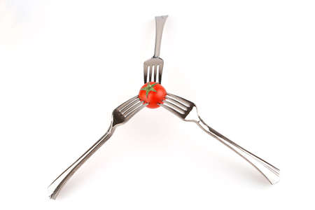 three forks and tomato over white background