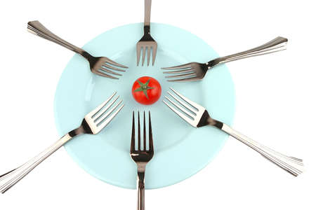 forks and tomato on blue dish over white