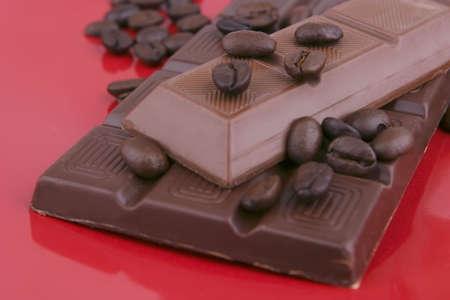 glas: dark chocolate bar on red ceramic dish close up