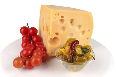 big chunk of yellow cheese with gold olives and tomatoes photo