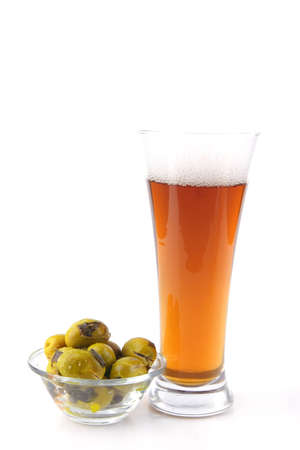 beer glass over white with gold olives photo
