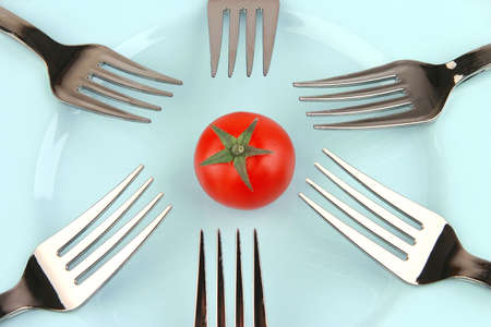 forks and tomato on blue dish over white photo
