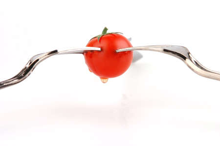 three forks and tomato over white background photo