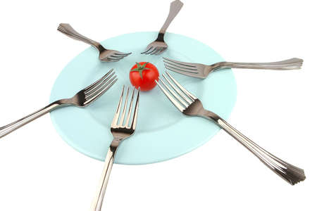 tomato and forks on dish over white