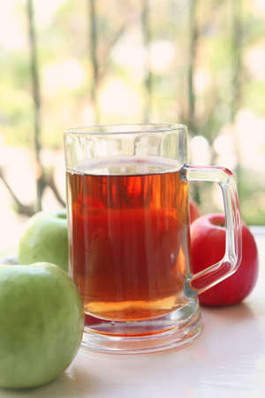 apple juice inside big glass with raw apples photo
