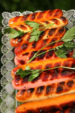 chorizos asados: salchichas asadas a la placa de cristal con perejil Foto de archivo