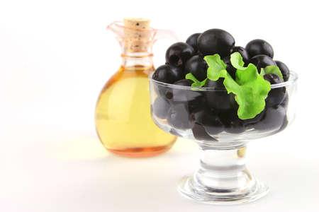 black olives inside small transparent bowl photo