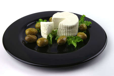 soft feta cheese on black dish with gold olives photo