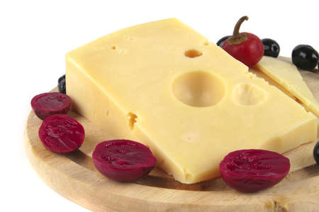 yelllow: fresh yelllow cheese on wooden plate over white