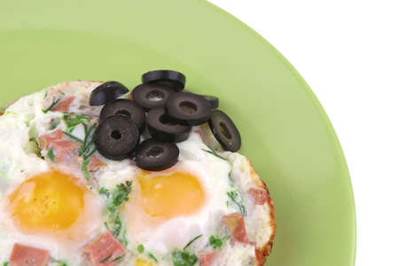 fried eggs and black olives on green dish photo