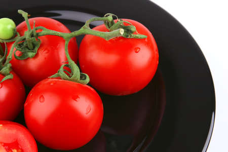 fresh uncooked tomato close up over black photo