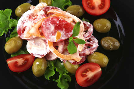 tomatoes salad and olives on black dish photo