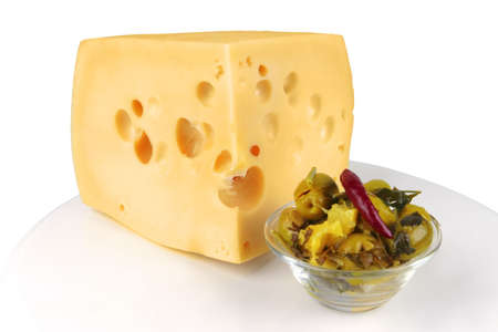 big chunk of yellow cheese with gold olives photo