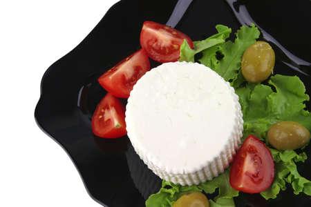 soft feta cheese on black dish over white photo