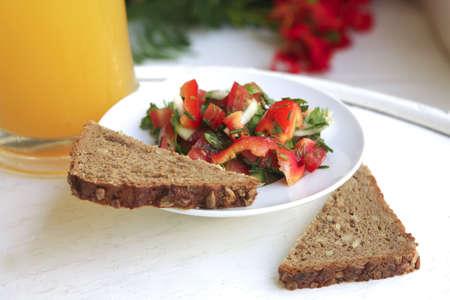 tomato salad and orange juice on white salad photo
