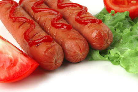 sausages served over white iwth tomato salad and ketchup photo