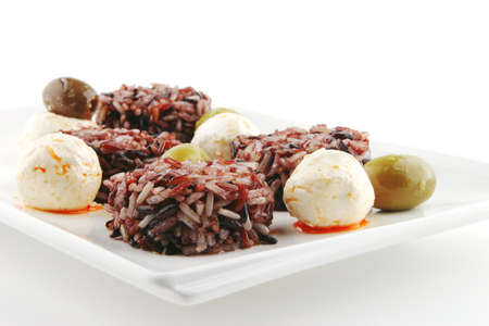 mozarella cheese and dark rice served on plate photo