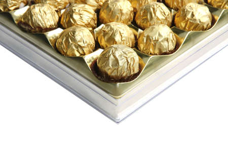 candy in golden foil over white background photo