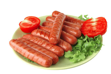 grilled sausages served on green dish wtih salad and tomato photo