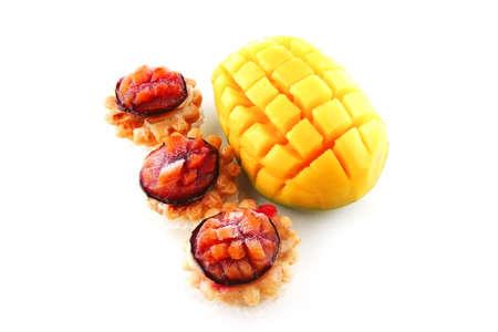 fresh ripe mango and small fruit pies served photo