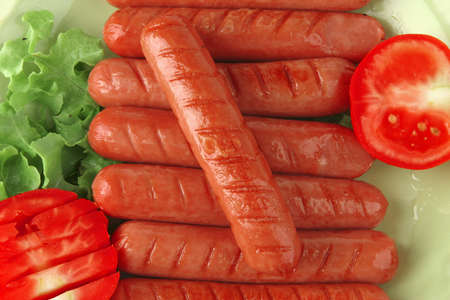 veal sausage: grilled sausages served on green dish wtih salad and tomato Stock Photo