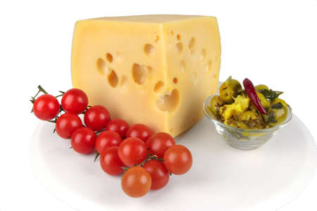 big chunk of yellow cheese with olives and tomatoes photo