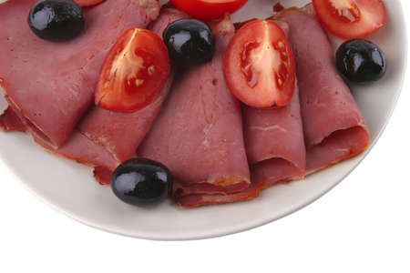 served sausage sliced with black olives over white photo